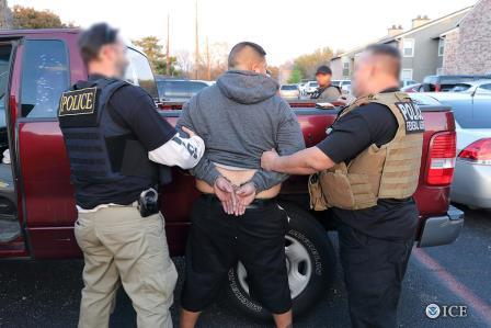ICE photo of officers with man in handcuffs
