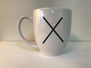 Coffee mug with a black X.