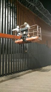 Two U.S. soldier apply paint to border wall. Dept. of Defense Photo.
