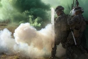 Soldiers in riot gear surrounded by smoke. U.S. Dept. of Defense photo.