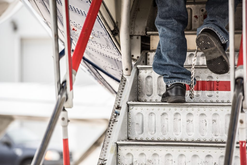View of feet of illegal alien in shackles walking up steps to a plane.